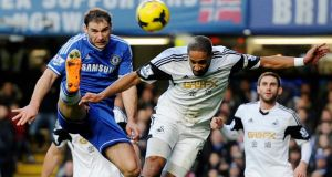 Chelsea's Branislav Ivanovic vies for the ball with Swansea's Ashley Williams (R) during the English Premier League clash at Stamford Bridge. Photo: Andy Rain/EPA