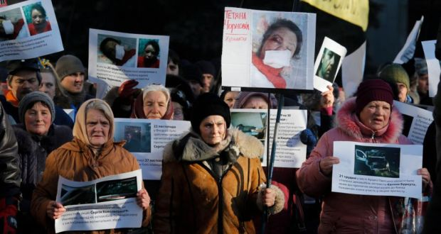 Protesters hold images depicting the badly beaten face of Ukrainian journalist Tetyana Chornovil during a protest in front of the interior ministry building in Kiev yesterday.  Photograph:  Sergey Dolzhenko/EPA