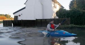 A man paddles his canoe past a flooded property in Yalding, southern England, yesterday . Photograph: Reuters/Luke MacGregor