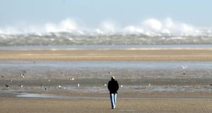 A walker looks at large waves from the beach at Sandymount in Dublin. Photograph: Alan Betson/The Irish Times