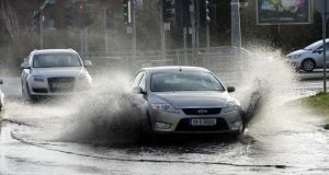 Cars drive through flooding on the Malahide Road near Clarehall, Dublin yesterday following heavy overnight rain. Photograph: Alan Betson/The Irish Times