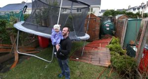 Malachy Duggan with his two year old daughter Easkey with the trampoline which appeared in his back garden yesterday at Binn Bhan, Knocknacarra, Galway, after the storm. Photograph: Joe O'Shaughnessy