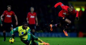 Ashley Young is challenged by Sebastien Bassong during the match at Carrow Road. Photograph: Jamie McDonald/Getty Images