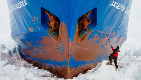 A crew member inspecting the hull of the ice-ensconced Akademik Shokalskiy. Photograph: Andrew Peacock/Reuters