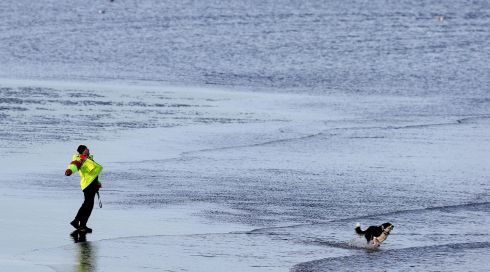 A man walks a dog on the sea front in Malahide, Dublin, following heavy rain and strong winds over the past week. Photograph: Brian Lawless/PA Wire