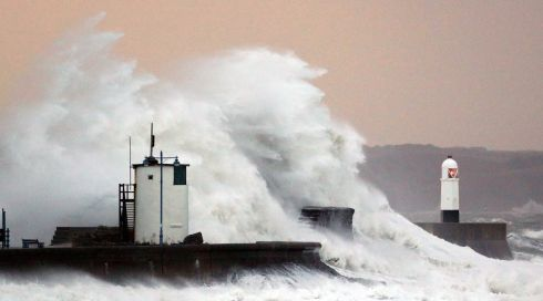 Huge waves crash  against the lighthouse wall in Porthcawl, south Wales. Photograph: Dimitris Legakis/EPA