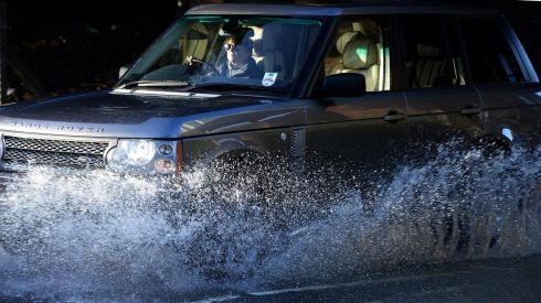A vehicle drives through flood waters in Leatherhead, Surrey, southwest of London. Photograph: Andy Rain/EPA