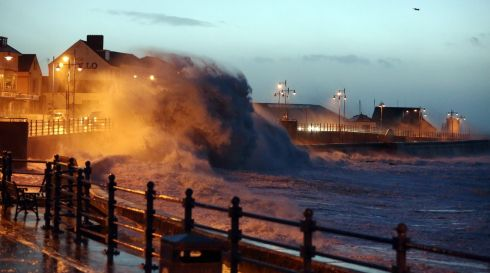 As dawn breaks huge waves crash  against the promenade wall in Porthcawl, south Wales. Photograph: Dimitris Legakis/EPA