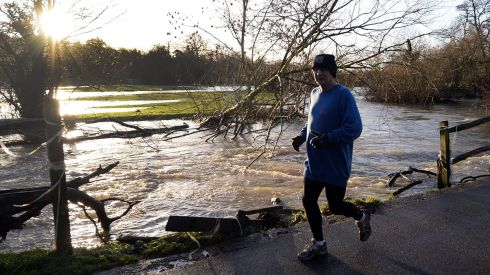 A man jogs along the swollen river Mole in Leatherhead, Surrey, southwest of  London. Photograph: Andy Rain/EPA