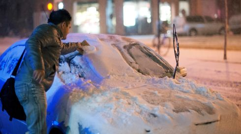 A man scrapes snow and ice off the windshield of his car on a street in New York. Photograph:  Sebastian Gabriel/EPA