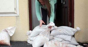 A woman places sandbags in the Sailorstown area of Belfast city centre in recent days. In Cork, homeowners and businesspeople along the South Mall and Oliver Plunkett Street as well as connecting side streets such as Princes Street, Cook Street, Marlborough Street and Pembroke Street had been  keeping sandbags at the ready for tonight. Photograph: Paul Faith/PA Wire