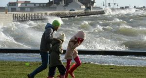 Battling the wind as the high tide inundates the promenade today at Clontarf, Dublin. Photograph: Dara Mac Dónaill/The Irish Times