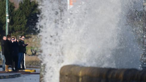 Bystanders watch the waves from Sandymount's coast road in Dublin.  Photograph: Cyril Byrne/Irish Times