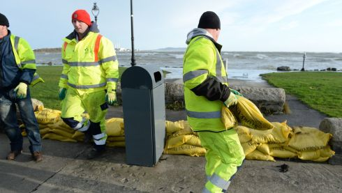 Council workers prepare for the high tides off Sandyount, Dublin.  Photograph: Cyril Byrne/Irish Times