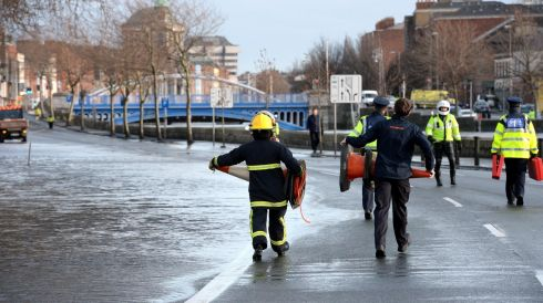 Gardai and Dublin Corporation workers block off the flooded area of Wolf Tone Quay in Dublin due to the Liffey's high tide. Photograph: Brenda Fitzsimons/Irish Times
