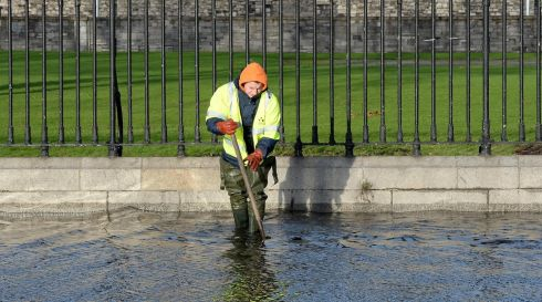 Dublin Corporation worker checks blockages on the road at Wolf Tone Quay in Dublin where the Liffey flooded the road due to a high tide and heavy rain. Photograph: Brenda Fitzsimons/Irish Times