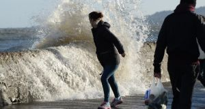 Dodging the waves at high tide on Sandymount's coast road today. Photograph: Cyril Byrne/The Irish Times