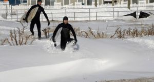 Plucky surfers plough  through  snow on Rockaway Beach, New York, today. Photograph: Andrew Gombert/EPA