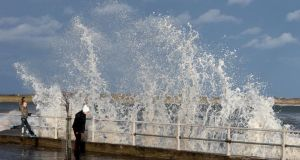 People walk past as waves crash onto the Coast Road in Malahide, Dublin, today. Photograph: Brian Lawless/PA Wire