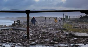 People assessing the damage caused by  storm force winds and high tides at   Rossbeigh Beach, Co Kerry. Photograph: Valerie O'Sullivan