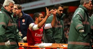 Theo Walcott of Arsenal makes a '2-0' gesture to the Tottenham fans as he is stretchered off the pitch at Emirates Stadium. Photograph:  Clive Rose/Getty Images