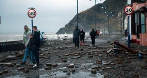 Locals walk through the debris-ridden promenade in Aberystwyth, West Wales, after taking a battering from waves driven by storm-force winds. Photograph: EPA/Dimitris Legakis