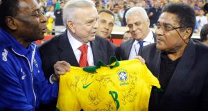 Soccer greats Pele (left) of Brazil and Eusebio (right) of Portugal hold a signed Brazil jersey in front of president of Brazil's soccer federation Jose Maria Marin before an international friendly match between Brazil and Portugal in September 2013. Photograph: Reuters