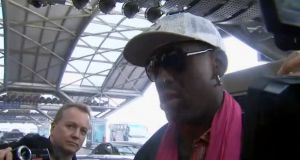 Broadcaster Matt Cooper (left) appears in the frame as Dennis Rodman is interviewed by journalists in Beijing. Image: Sky News
