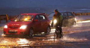 A cyclist makes his way through the flooded road at Salthill, Galway this morning during the high tide. Photograph: Joe O'Shaughnessy.