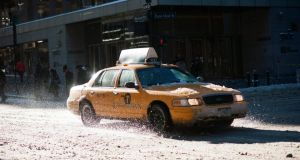 "A taxi drives through snow at Madison Avenue in New York. The eastern half of the US has been hit by a dangerously cold whirlpool of dense air known as a ""polar vortex"" which threatens to break decades-old weather records. Photograph: Sebastian Gabriel/EPA"