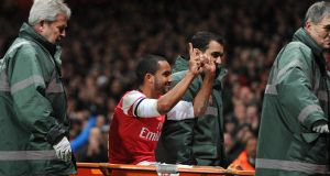 Arsenal's Theo Walcott taunts Tottenham Hotspur fans with the current match score as he is stretchered off the pitch injured during Saturday's FA Cup third round tie at the Emirates  Stadium. Photograph:  Adam Davy/PA Wire.