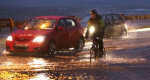 A cyclist makes his way through the flooded road at Salthill yesterday  morning during the high tide and stormy winds. Photograph: Joe O'Shaughnessy