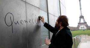 "French author Marek Halter cleans the word 'quenelle' written on ""The Wall For Peace"" at the Champs de Mars near the Eiffel Tower in Paris on Monday. Photograph: Reuters"