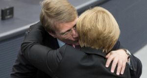German chancellor Angela Merkel  is congratulated by her outgoing chief of staff Ronald Pofalla after being re-elected in a vote session at the Bundestag. Photograph: David Gannon/AFP/Getty Images