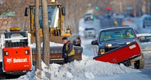 City workers use a variety of plows to remove snow from sidewalks in south Minneapolis. Photograph: Eric Miller/Reuters