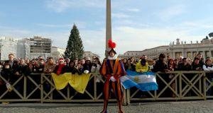 A Swiss Guard attends Pope Francis's Christmas Day message from the central balcony of St Peter's Basilica.