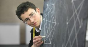 "Paul Clarke (17) from St Paul's college Dublin with exhibit ""Contributions to Cyclic Graph Theory"" in the RDS, yesterday. Photograph: Gareth Chaney/Collins"