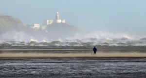 An angry looking sea churns under the Baily Lighthouse on Howth Head as a walker takes to the beach on Sandymount during the recent stormy weather. Photograph: Alan Betson/The Irish Times