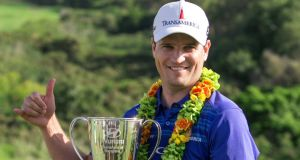 Zach Johnson holds the trophy after winning the Tournament of Champions in Kapalua, Hawaii,  on Sunday. Johnson will be the favourite at this week's Sony Open in Honolulu. Photograph: Marco Garcia/AP Photo