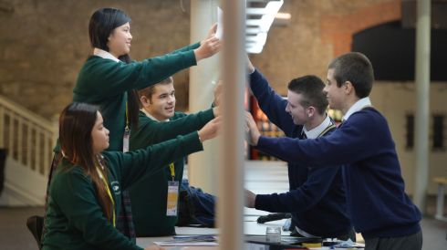 Rhane Cepres, Irene Pabinguit and Konrad Gladysz from St Laurence College, and Martin Poppmeier and Michael Cassidy from St Fintan's High School, setting up their projects.   Photograph: Alan Betson/The Irish Times