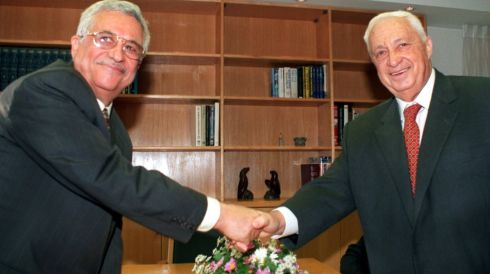Palestinian negotiator Mahmoud Abbas (left) and Israeli foreign minister Ariel Sharon turn to the cameras and smile as they shake hands at the start of their meeting in Sharon's office in Jerusalem in this file picture taken in November 1998. Photograph: Reuter/Files