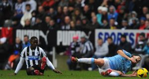 Newcastle player Mapou Yanga-Mbiwa (l) fouls Samir Nasri, who was later stretchered off  at St James's Park. Photograph:  Stu Forster/Getty Images
