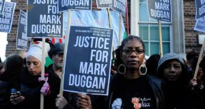 Friends and family of Mark Duggan hold a vigil outside Tottenham police station in London on Saturday. Photograph: EPA/Andy Rain