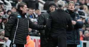 Newcastle head coach Alan Pardew (centre) is stopped from arguing with Manchester City head coach Manuel Pellegrini (right) at  St James' Park