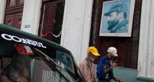 Men walk under a portrait of former Cuban president Fidel Castro in Havana. Since last month, Cubans have had access to automatic cash machines for the first time and  can provide accommodation for tourists and visitors. Photograph: Enrique de la Osa/Reuters