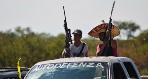 Vigilantes stand on a pick up truck on the outskirts of Paracuaro on January 10th. Mexico's government on Monday pledged to take control of the violent western state of Michoacan after days of fighting between masked vigilantes and members of one of the country's most powerful drug cartels. Photograph: Alan Ortega/Reuters