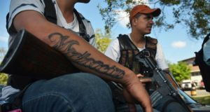 A vigilante sports a tattoo that reads 'Michoacan' while sitting with others on the outskirts of Paracuaro on January 10th. Photograph: Alan Ortega/Reuters