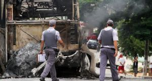 Policemen pass by a burnt bus  in Campinas, Brazil, on Monday. People torched buses and attacked cars in protest against the killing  of 12 people in a surge of violence that began with the murder of an off-duty policeman. Photograph: Denny Cesare/AFP/Getty Images
