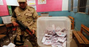 An Egyptian  soldier stands guard yesterday as officials count ballots after polls closed during the final stage of a referendum on Egypt's new constitution at the constitutional referendum commission in Cairo. Photograph: Mohamed Abd El Ghany/Reuters
