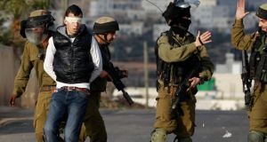 Israeli soldiers arrest a Palestinian during clashes with Israeli troops at a protest against the Jewish settlement of Ofra, in the West Bank village of Silwad, near Ramallah, yesterday. Photograph: Mohamad Torokman/Reuters